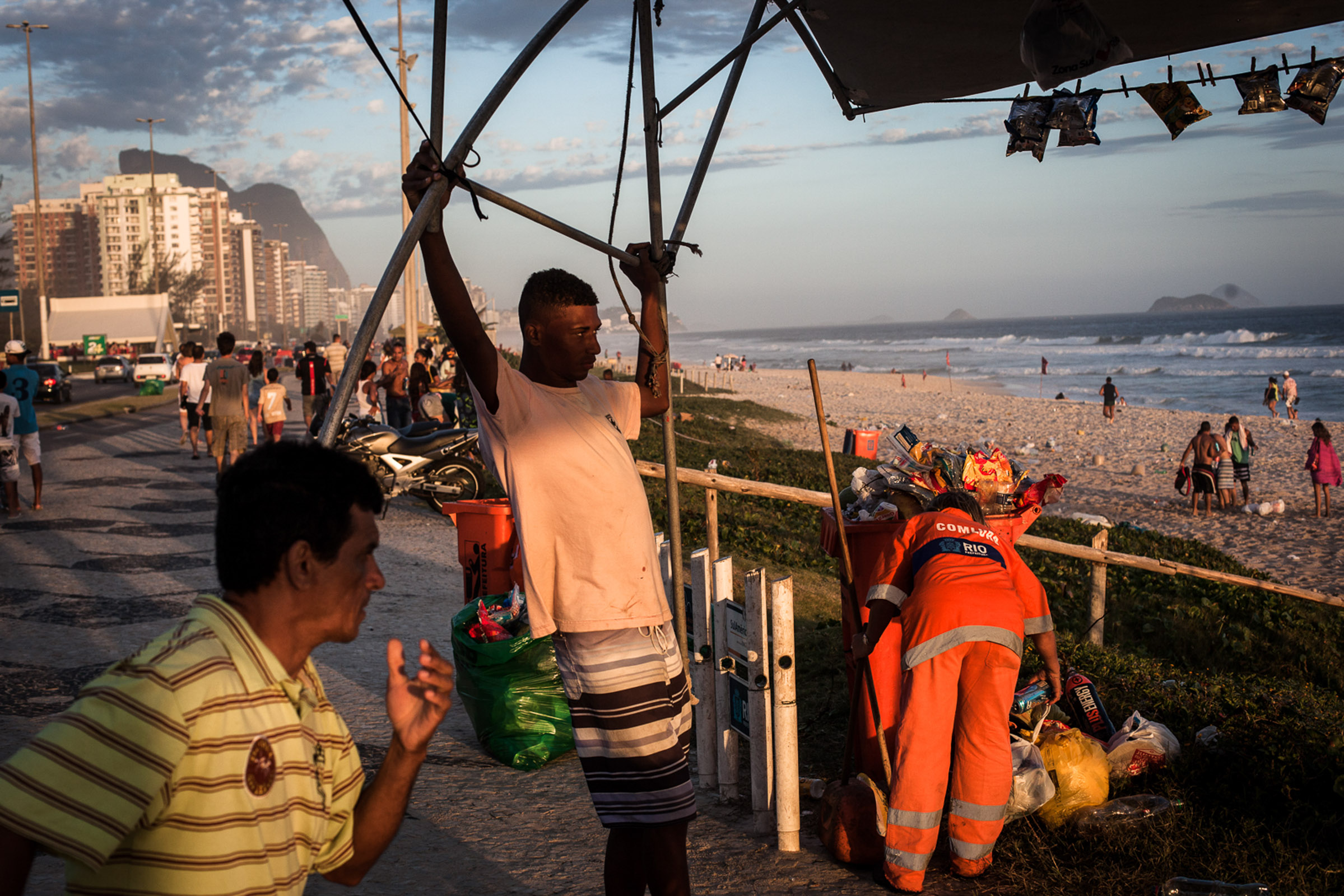 Rio de Janeiro, le 15 Novembre 2013. Fin de journée sur la plage de Barra da Tijuca. Une femme gari commence le nettoyage de la plage.  Rio de Janeiro, November 15, 2013. End of the day on the beach in Barra da Tijuca. A Gari  woman starts cleaning the beach.