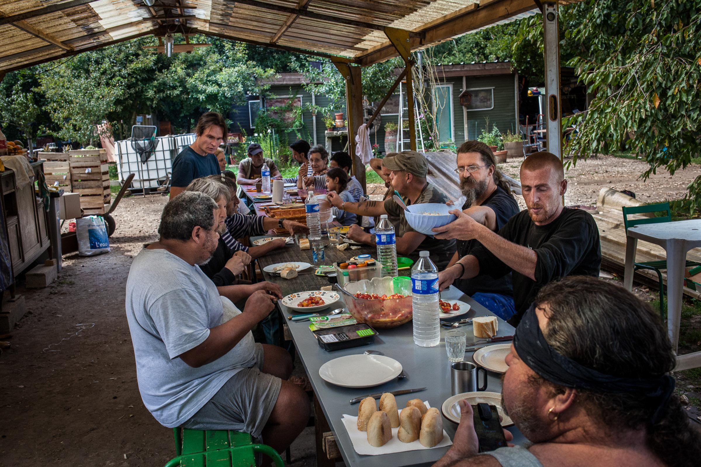 """Villebéon, le 19 Aout 2014. Repas communautaire dans l'un des bâtiments """"en dur"""" du village.   Villebéon, August 19, 2014. Community meal in the dining """"room""""."""