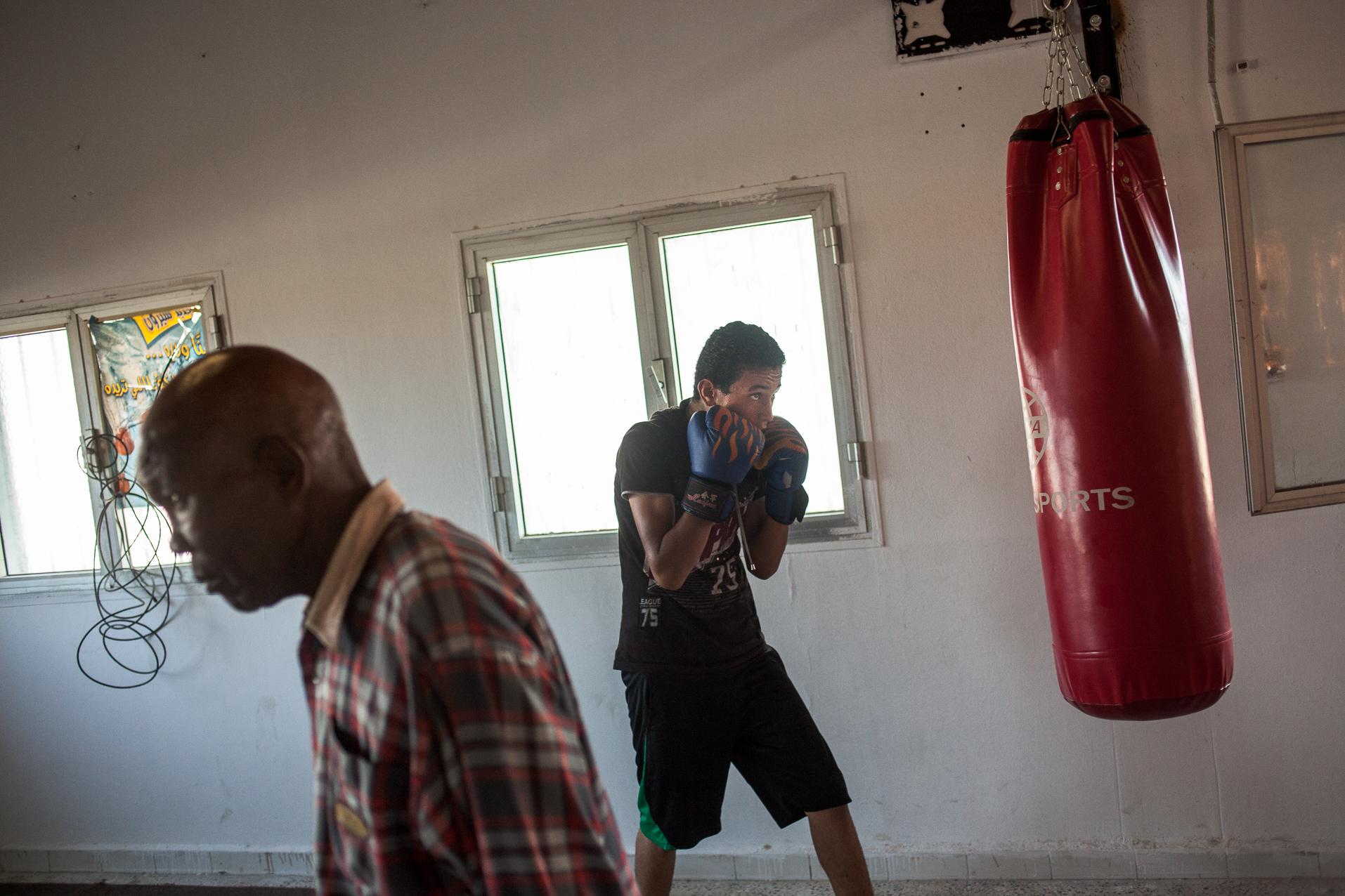 """Tripoli, Juillet 2012. Interdite depuis 1979 par Muammar Kadhafi qui trouvait ce sport """"sauvage"""", la boxe revient en Libye. Les jeunes de ce quartier du sud Ouest de Tripoli s'entrainent sous la houlette d'anciens champions.  Tripoli, July 2012. Prohibited since 1979 by Muammar Gaddafi, boxing returns to Libya. Young people of this district in the south west of Tripoli are training under the guidance of former champions."""