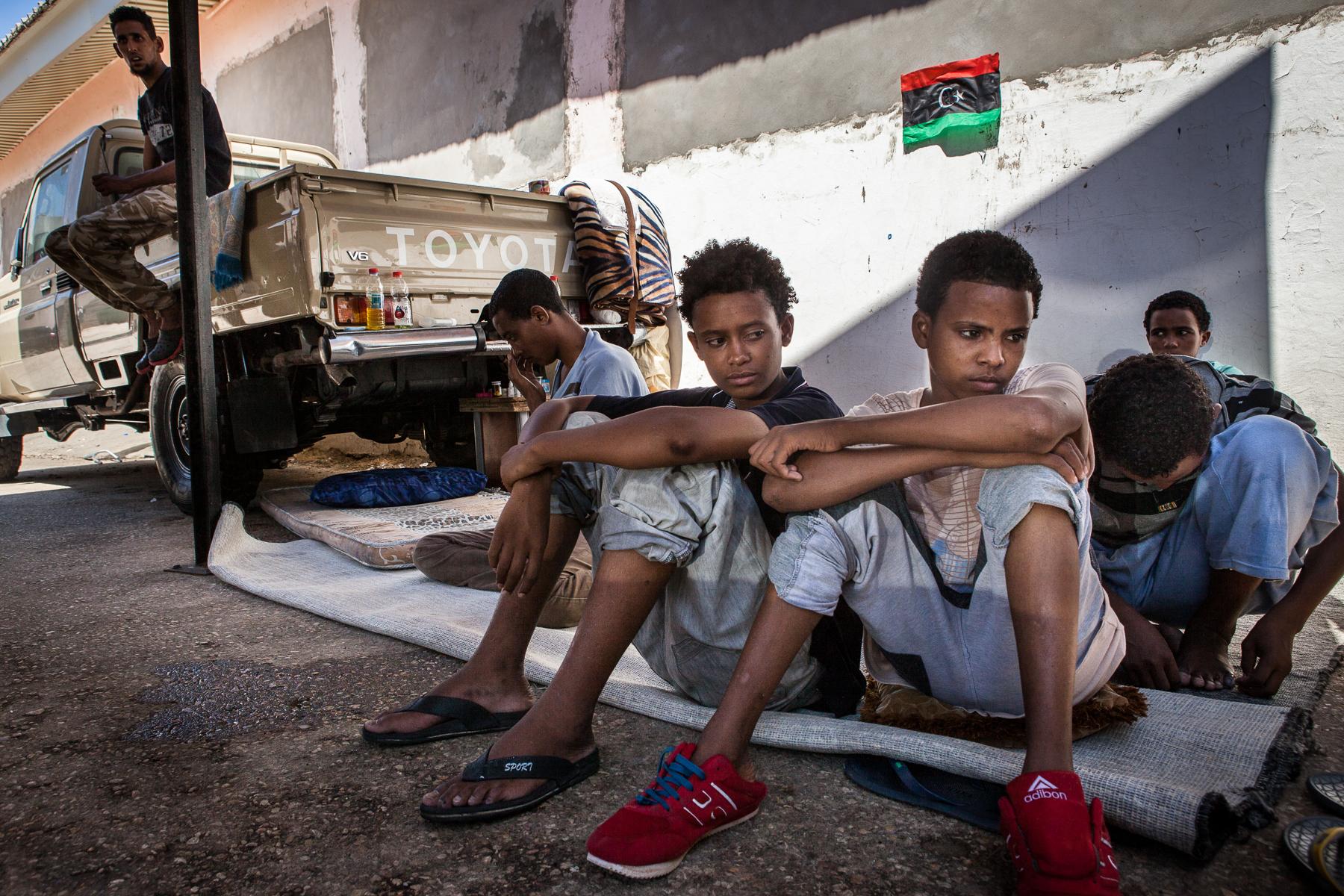 Tripoli, le 8 Juillet 2015. Mineurs isolés erythréens vivant dans le Centre de détention pour migrants illégaux dans le quartier général du département de lutte contre la migration illégale. Le gouvernement de Fajr Libya, installé à Tripoli, est en recherche de reconnaissance de la part de la communauté internationale. Conscients que les conditions de vie dans les camps sont difficiles, ils demandent de l'aide financière et logistique à l'occident pour réussir à gérer la migration illégale transitant par son territoire. En attendant, les migrants illégaux sont entassés dans des lieux insalubres, sans possibilité de sortir ni d'avoir suffisamment accès aux soins.   Tripoli, July 8, 2015. Eritrean migrant children  in the Detention Center, the headquarters of the Department of fight against illegal migration. The government of Fajr Libya, based in Tripoli, is looking for recognition from the international community. Aware that the living conditions in the camps are difficult, they ask for financial and logistical assistance to the West to successfully manage illegal migration transiting through its territory. Meanwhile, illegal migrants are crammed in unhealthy places, not allowed to go out or to have sufficient access to care.