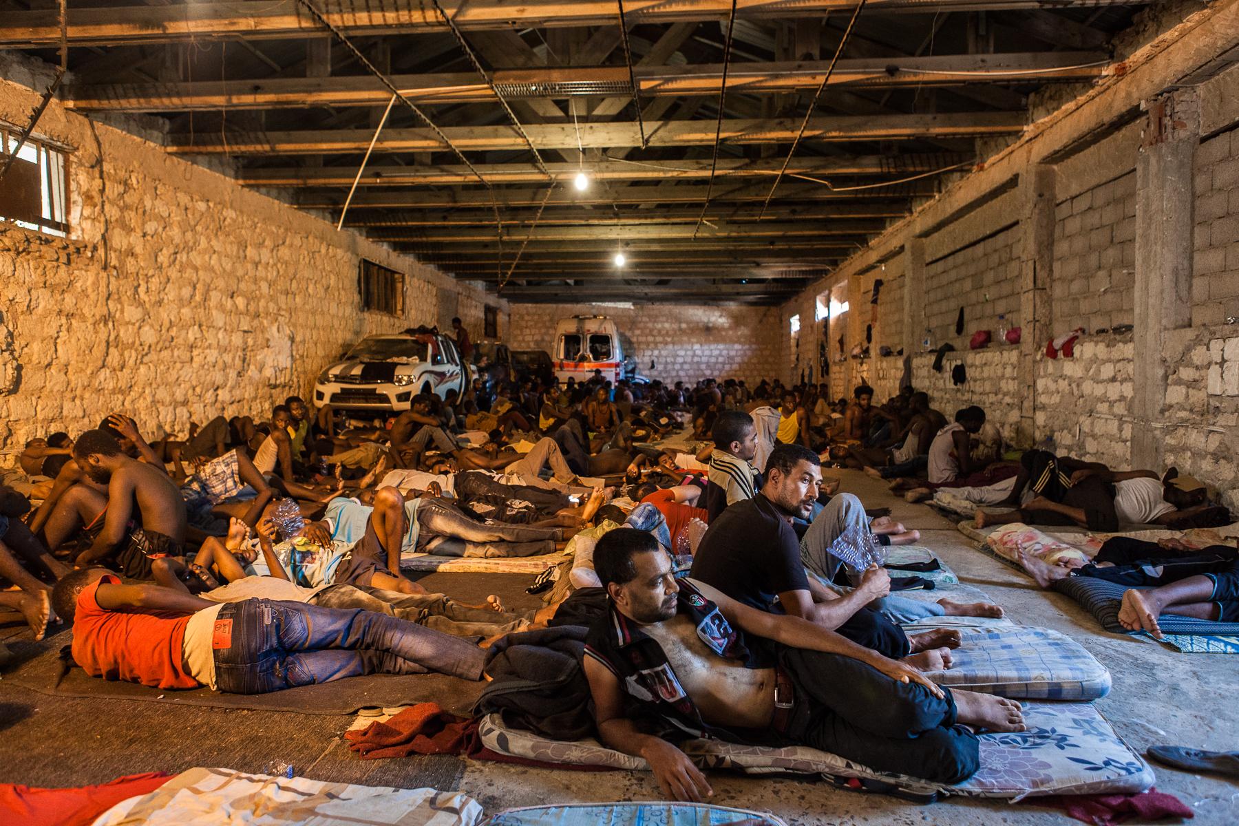 Tripoli, le 8 Juillet 2015. Centre de détention pour migrants illégaux dans le quartier général du département de lutte contre la migration illégale. Le gouvernement de Fajr Libya, installé à Tripoli, est en recherche de reconnaissance de la part de la communauté internationale. Conscients que les conditions de vie dans les camps sont difficiles, ils demandent de l'aide financière et logistique à l'occident pour réussir à gérer la migration illégale transitant par son territoire. En attendant, les migrants illégaux sont entassés dans des lieux insalubres, sans possibilité de sortir ni d'avoir suffisamment accès aux soins.   Tripoli, July 8, 2015. Detention Center in the headquarters of the Department of fight against illegal migration. The government of Fajr Libya, based in Tripoli, is looking for recognition from the international community. Aware that the living conditions in the camps are difficult, they ask for financial and logistical assistance to the West to successfully manage illegal migration transiting through its territory. Meanwhile, illegal migrants are crammed in unhealthy places, not allowed to go out or to have sufficient access to care.
