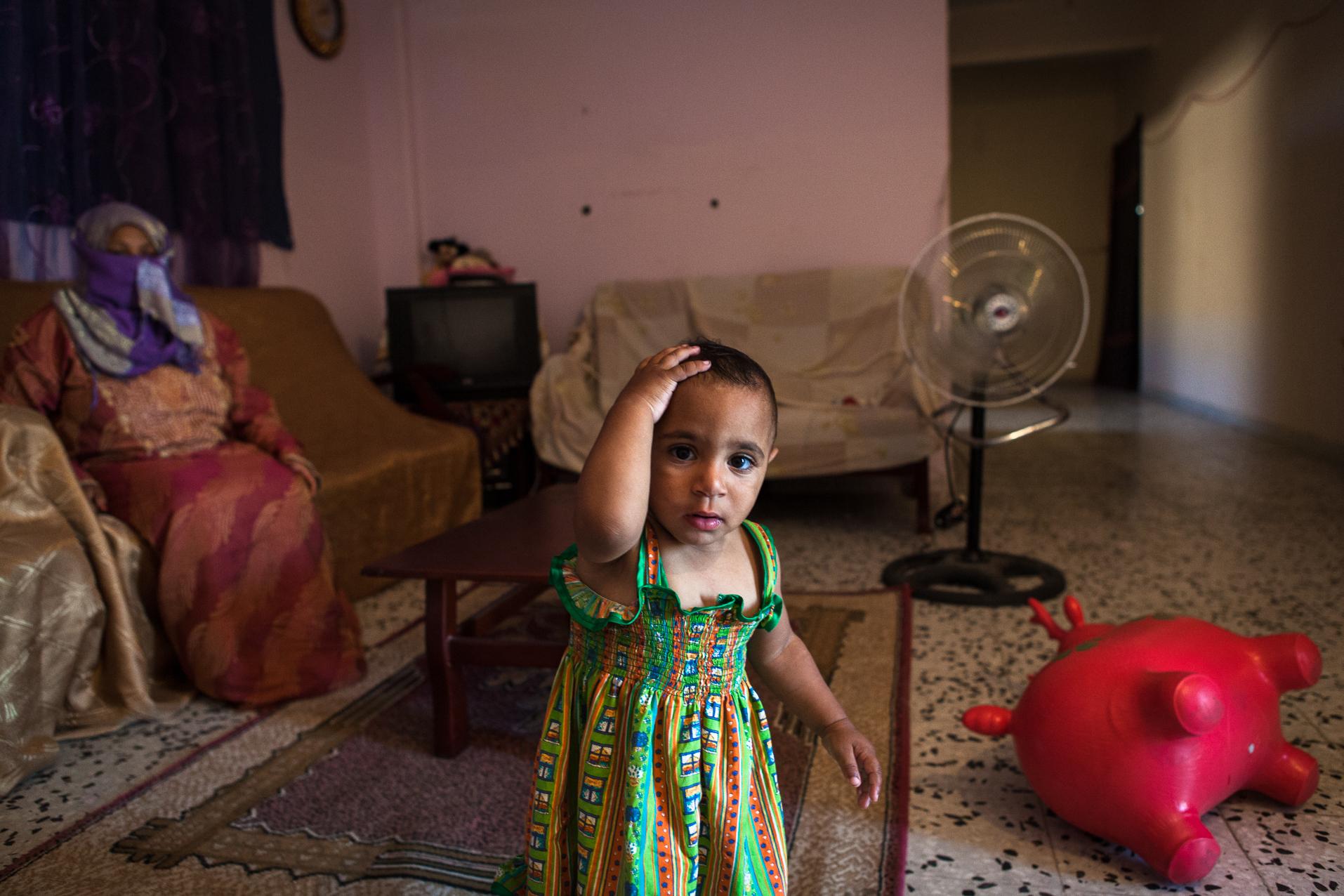"""Tripoli, 27 Juin 2012. Bab-al-Azizia, ancien bastion de Kadhafi au centre de Tripoli. Des familles démunies occupent les ruines de la place forte, devenue depuis un haut lieu de traffic (drogues, alcool, prostitution...). Cette femme dont le mari est très souvent absent doit s'occuper seule de sa fille handicapée. Un soir, elle sort de chez elle pour demander aux prostituées d'aller plus loin et d'arrêter le tapin. La nuit même, la façade de leur """"appartement"""" est mitraillé par les milices organisant les trafics dans le complexe. Face aux menaces, elle se dit prête à se battre pour protéger sa famille.  Tripoli, June 27, 2012. Bab al-Azizia, Gaddafi's former stronghold in central Tripoli. Poor families occupy the ruins of the fortress, which has since become a mecca for traffic (drugs, alcohol, prostitution ...). The woman whose husband is often absent, must take care of her disabled daughter alone. One night she came out the door to ask prostitutes to go further and stop the hustler. The same night, the facade of their """"apartment"""" was shot by the militia organizing traffic in the complex. Face of threats, she is willing to fight to protect her family."""