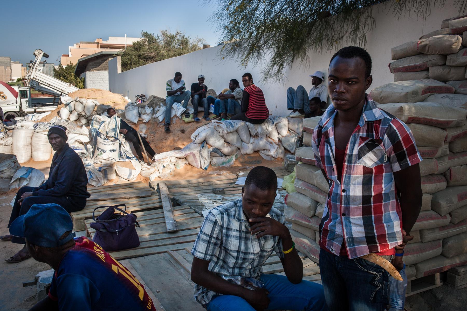 Tripoli, le 8 Juillet 2015. Dans certains quartiers de Tripoli, des migrants illégaux proposent leurs services sur le bord de la route. Maçons, peintres, électriciens, certains cherchent à gagner de l'argent pour envoyer à leur famille restée au pays, d'autres cherchent à accumuler de quoi payer le passage vers l'Europe. Tous s'accordent à dire que ces derniers mois, il y a de moins en moins de travail, et que les salaires ont été sérieusement réduits. Ils sont régulièrement victimes d'arnaques, de racket, voire d'enlèvements.   Tripoli, July 8, 2015. In some neighborhoods of Tripoli, illegal migrants are offering their services on the roadside. Masons, painters, electricians, some seek to earn money to send to their families back home, others are looking to accumulate money to pay the passage to Europe. All agree that in recent months, there is less and less work, and wages have been seriously reduced. They are regularly victims of scams, racketeering and even kidnappings.
